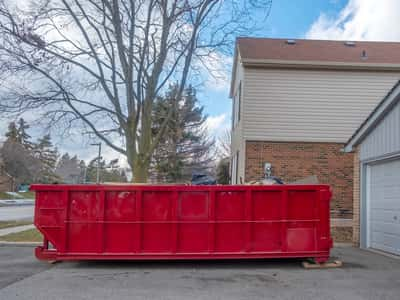 This is a picture of a 15 yard roll off dumpster rental in front of a home in the driveway. The home owners are doing a home kitchen remodel and are throwing away trash in the dumpster rental. This picture was taken in Evansville, Indiana.