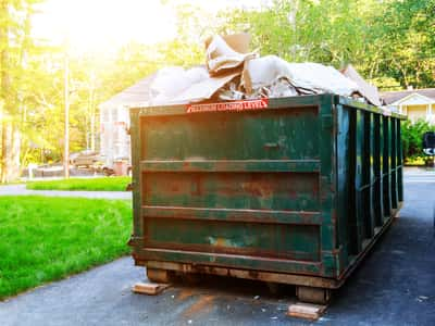 This is a picture of a 20 yard dumpster rental in the driveway of a residential home. This picture was taken in Evansville, Indiana.