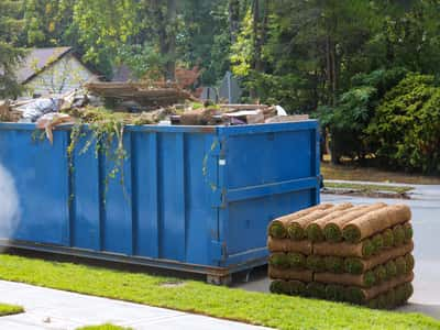 This is a picture of a 30 yard dumpster rental being used for a total home improvement renovation. There is a picture of fresh sod next  to the large dumpster rental. This picture was taken outside of a house in Evansville, Indiana.